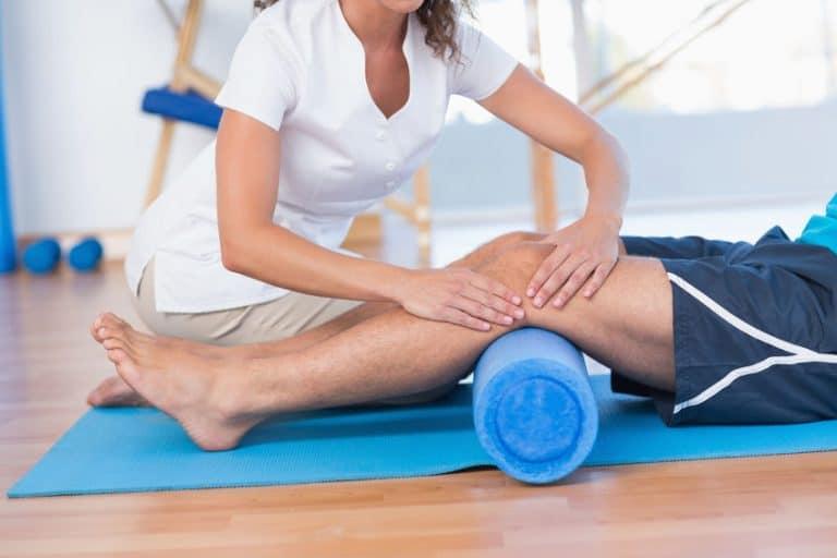 Imagem de pessoa fazendo fisioterapia com rolo de espuma.