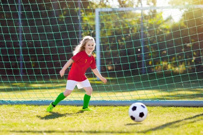 Criança jogando futebol.