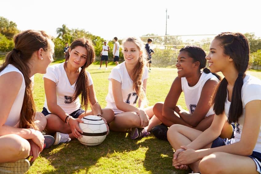 Imagem de meninas sentadas em campo de futebol com bola a frente.