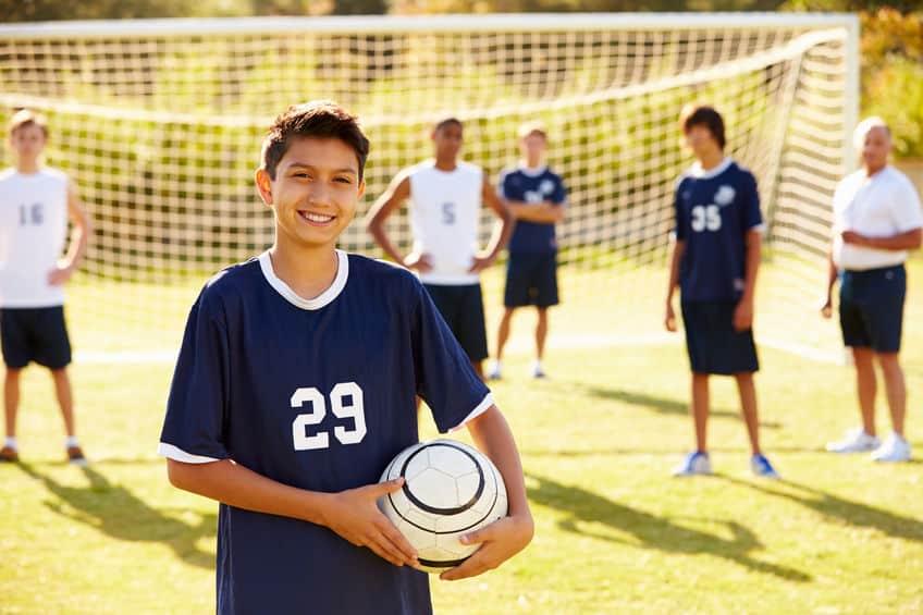 Imagem de meninos jogando futebol.