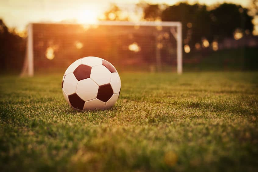 Bola de futebol em campo ao entardecer.