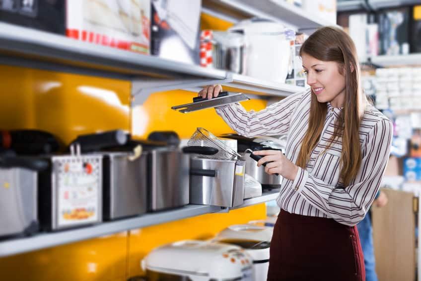 Mulher escolhendo fritadeira em loja.