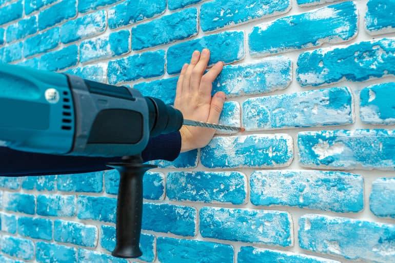Furando parede azul.