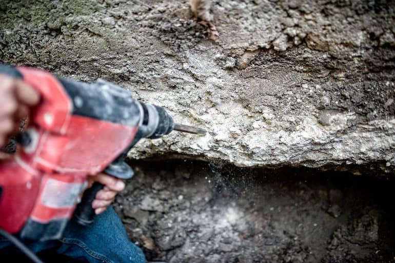 Imagem mostra pessoa furando pedra.
