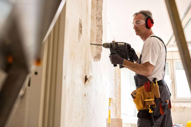 Homem trabalhando em obra com furadeira.