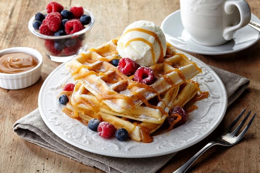 Waffle com frutas e sorvete e xícara de café ao fundo.
