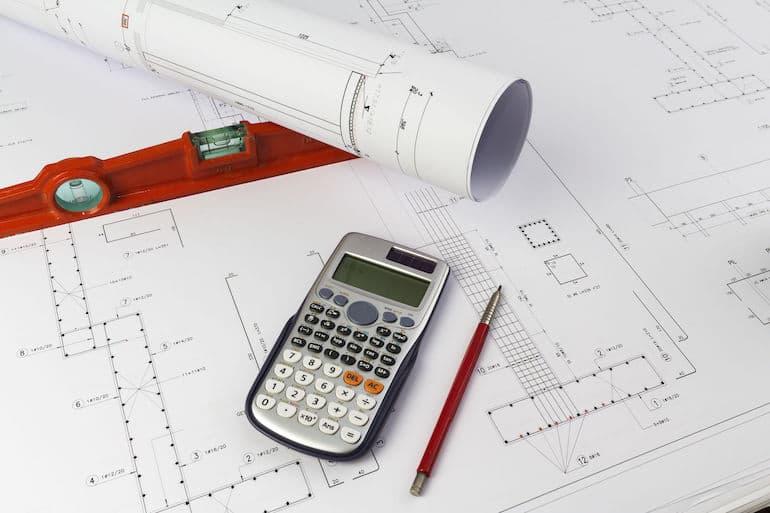 Fazendo medição com planta de imóvel, com caneta e calculadora ao lado.