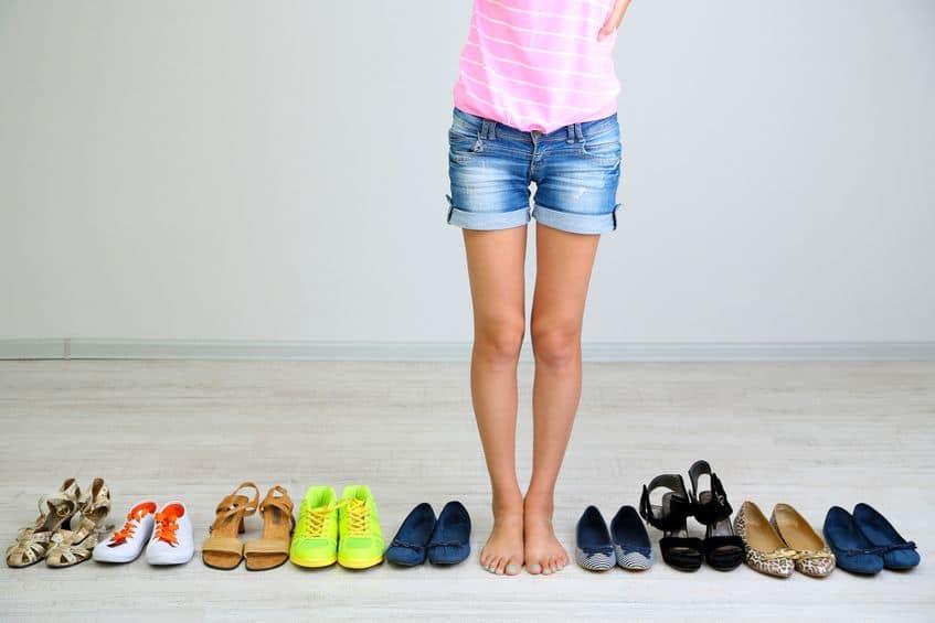 Imagem de mulher com vários pares de sapato ao lado.