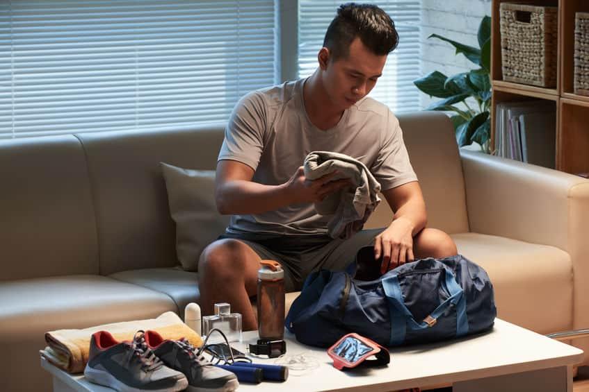 Imagem de homem guardando roupas em bolsa.