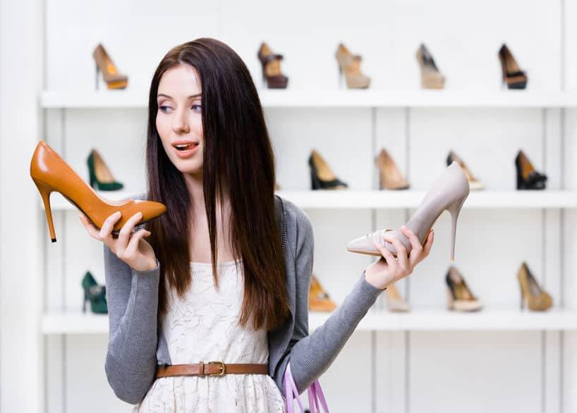 Mulher segurando sapatos.