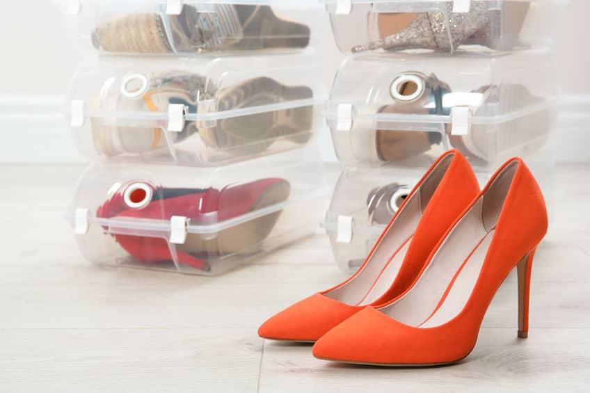 Imagem de caixas com sapato e sapato laranja a frente.