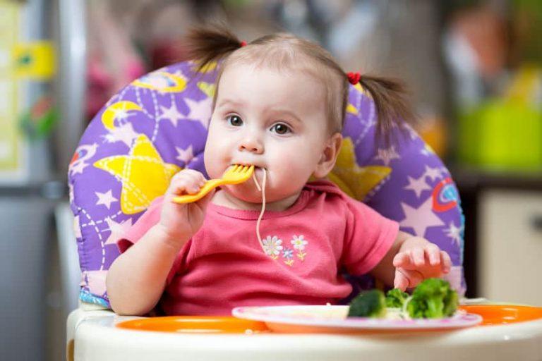 Menina comendo com garfo.