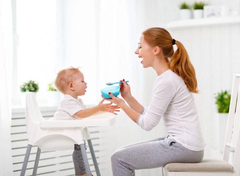 Mãe dando comida para o filho, que está em cadeira de alimentação.