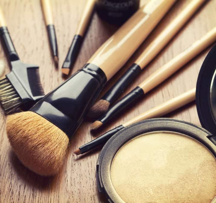 Imagem mostra alguns pinceis de maquiagem ao lado de um iluminador