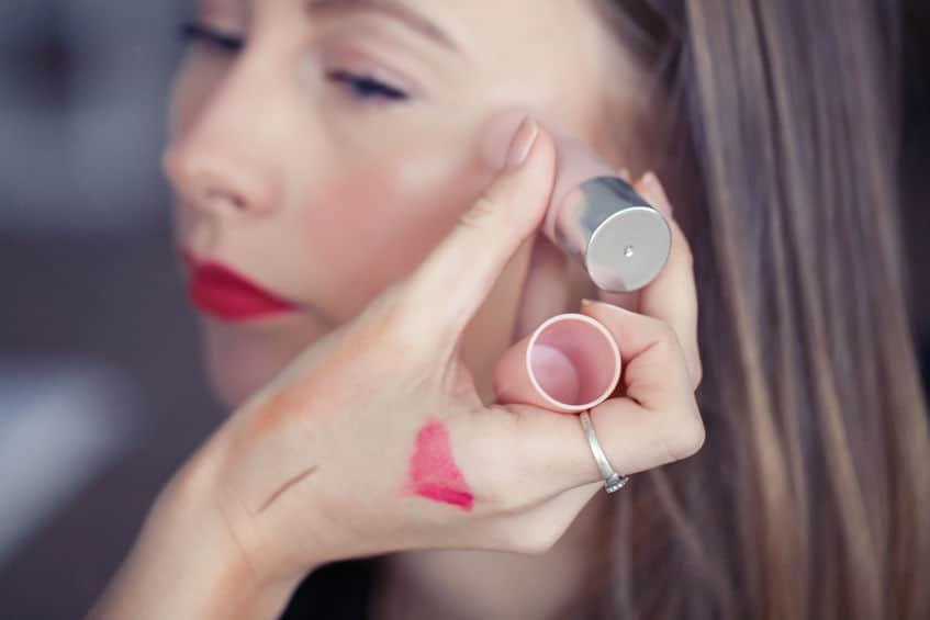 Imagem mostra alguém aplicando iluminador sobre a pele de uma mulher