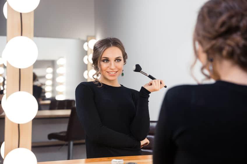 Imagem mostra uma mulher diante do espelho se maquiando