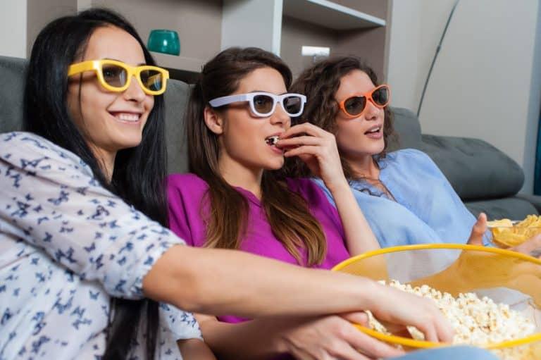 Imagem de mulheres assistindo TV e comendo pipoca.