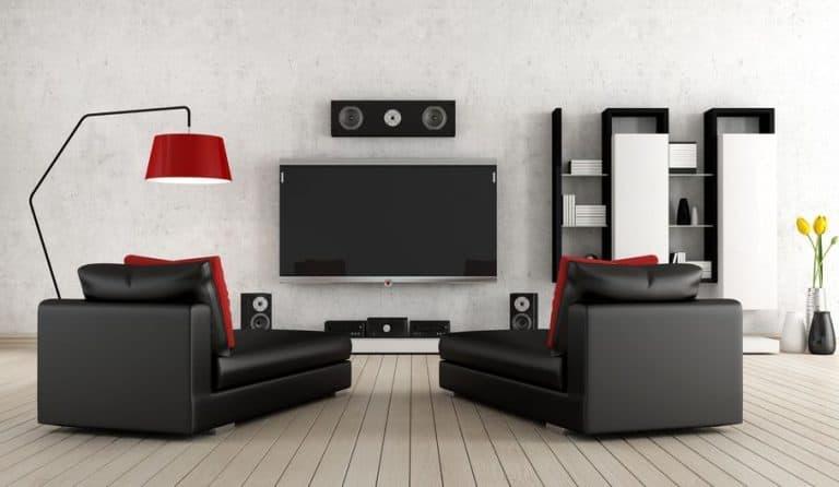 Imagem de sala com TV e home theater e sofás a frente.
