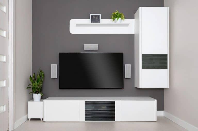 Imagem de TV com home theater e móveis brancos.