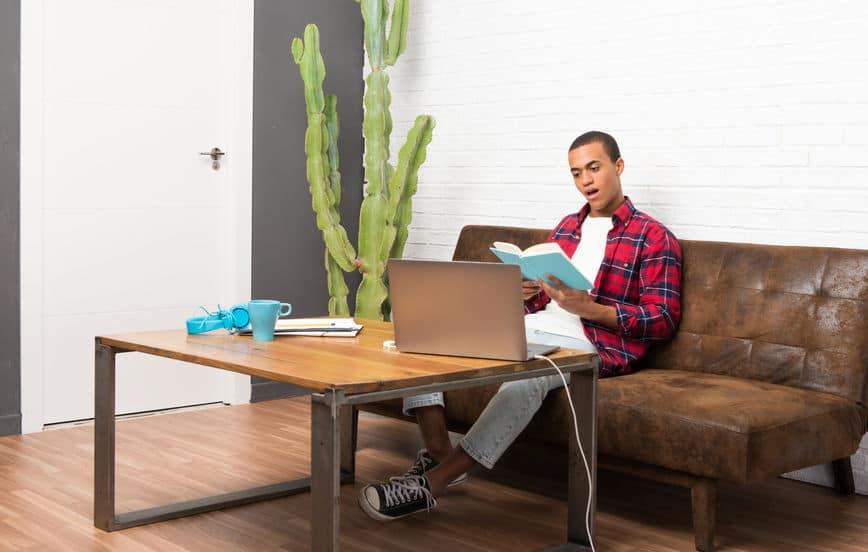 Imagem de homem sentado em sofá lendo.