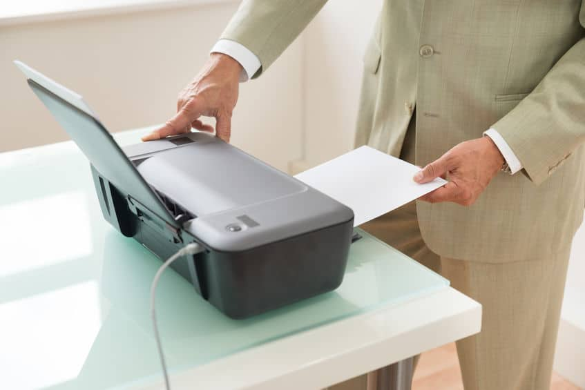 Homem utilizando impressora.