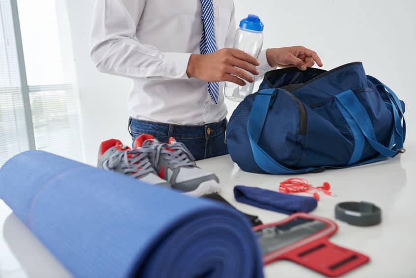 Imagem de homem guardando itens de academia em bolsa azul.