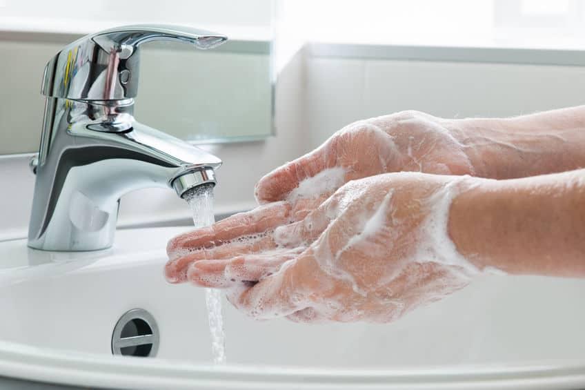 Imagem de pessoa lavando as mãos.