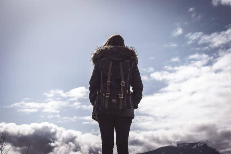 Mulher com mochila preta grande nas costas.