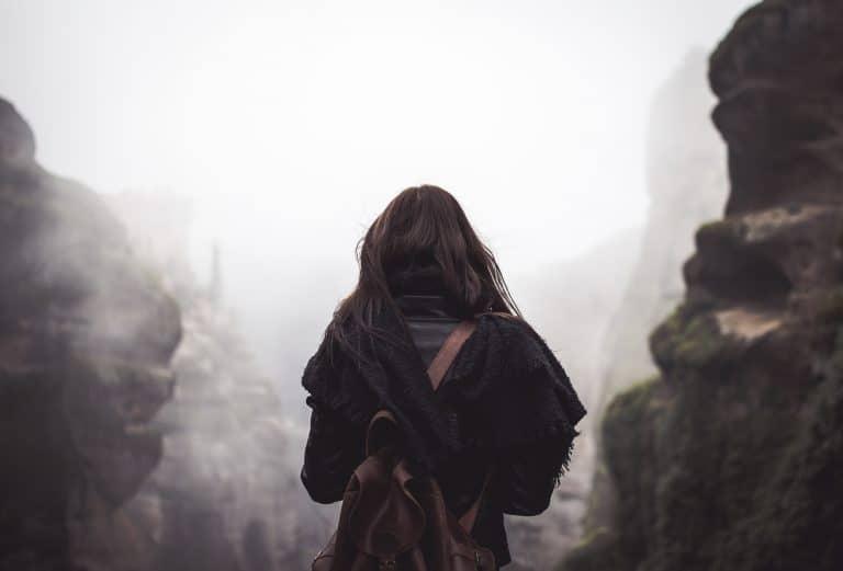 Mulher com roupa preta e mochila marrom.