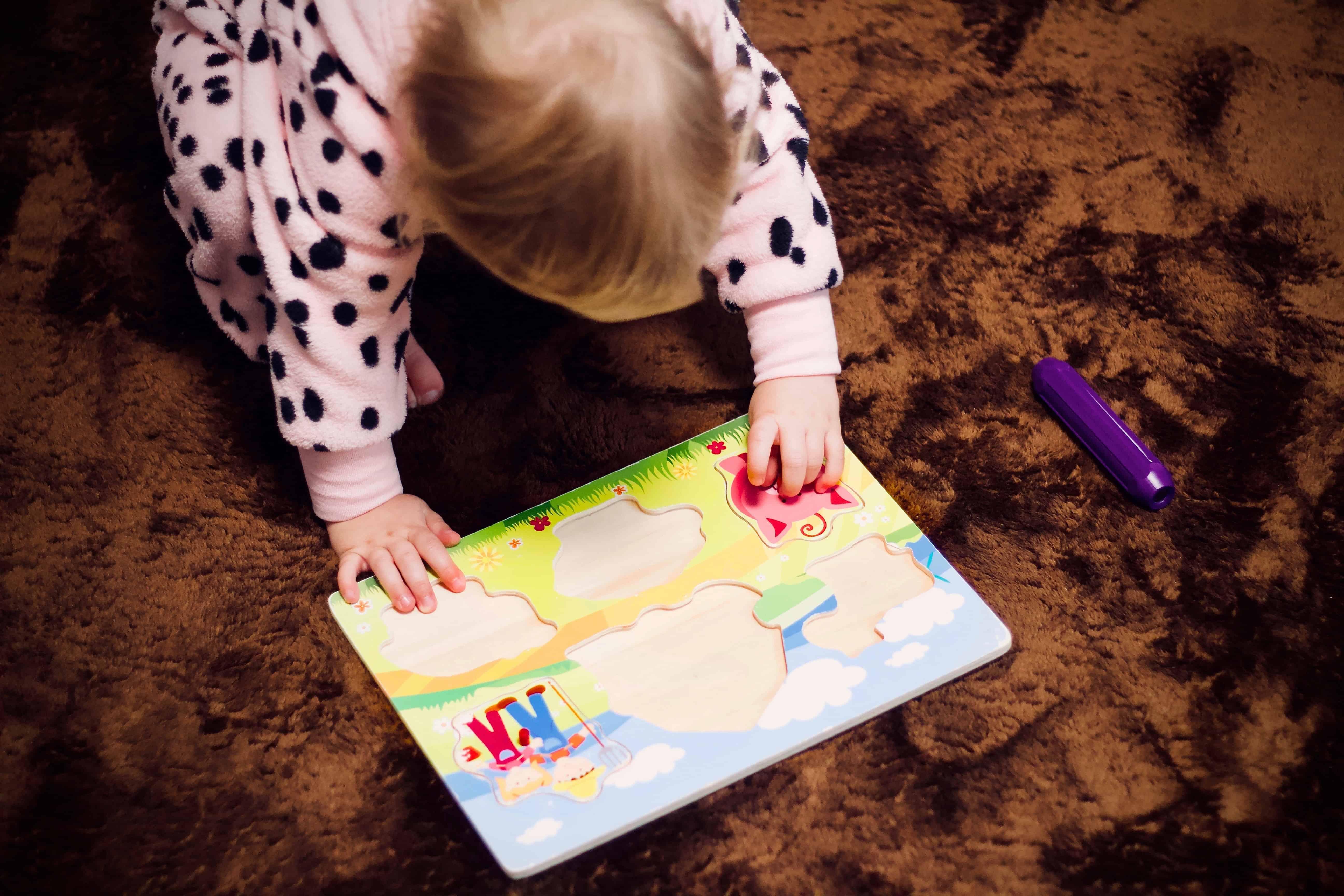 Imagem de bebê brincando com quebra cabeça.