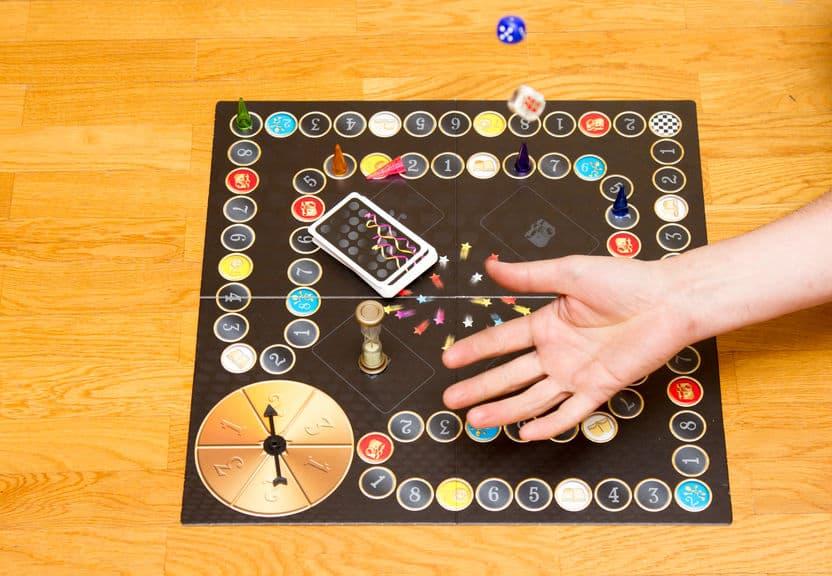 Imagem de mão jogando dado sobre tabuleiro.