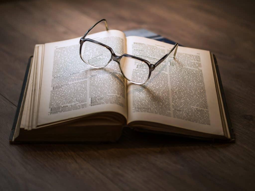 Imagem de óculos sobre livro.