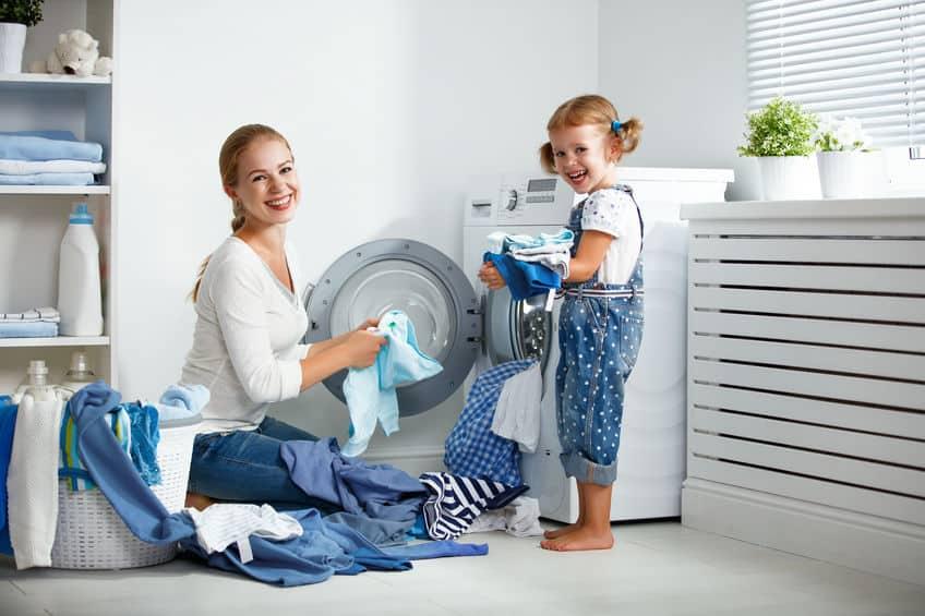 Imagem de mãe e filha colocando roupas na máquina.