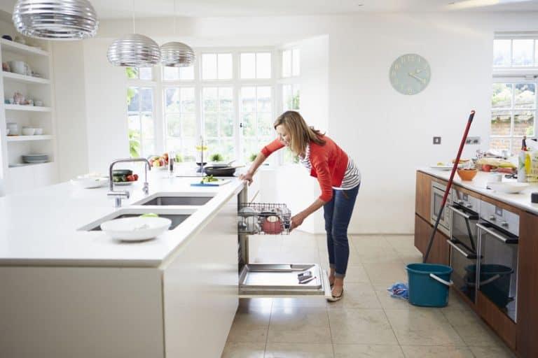 Mulher colocando louças na lavadora.