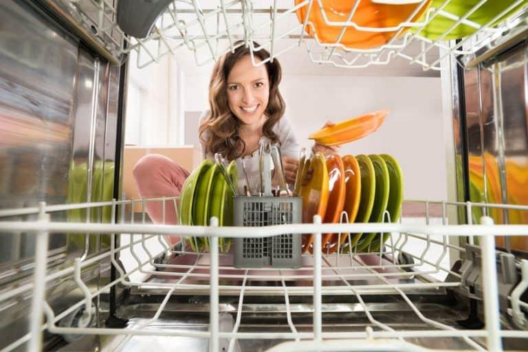Imagem de mulher verificando louças em lava-louças.