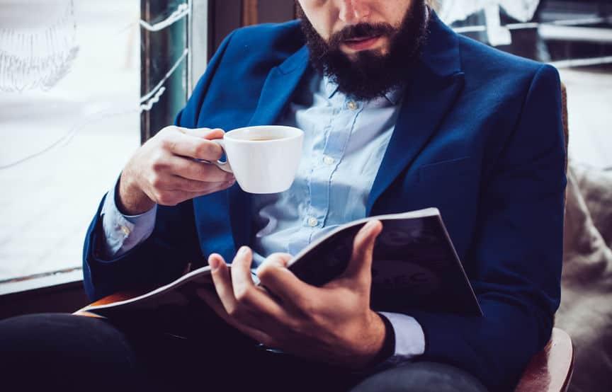 Imagem de homem lendo HQ e tomando café.