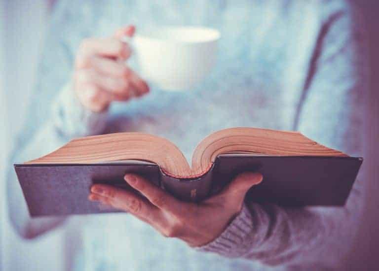 Mulher lendo livro e tomando xícara de café.