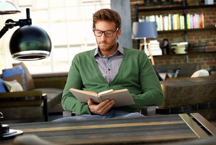 Imagem de homem sentado lendo livro.