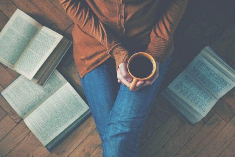 Mulher sentada no chão com livros em volta e segurando xícara de café.