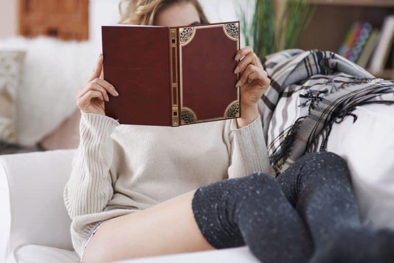 Mulher em sofá lendo livro.