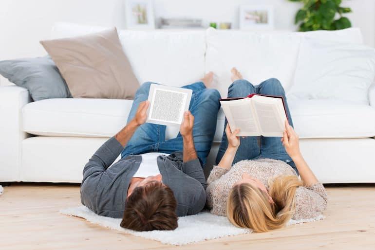 Casal deitado no chão lendo livro.
