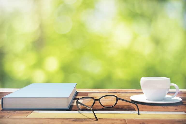 Livro sobre mesa ao lado de óculos e xícara.