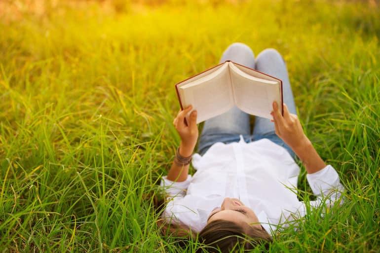 Mulher lendo livro em parque.