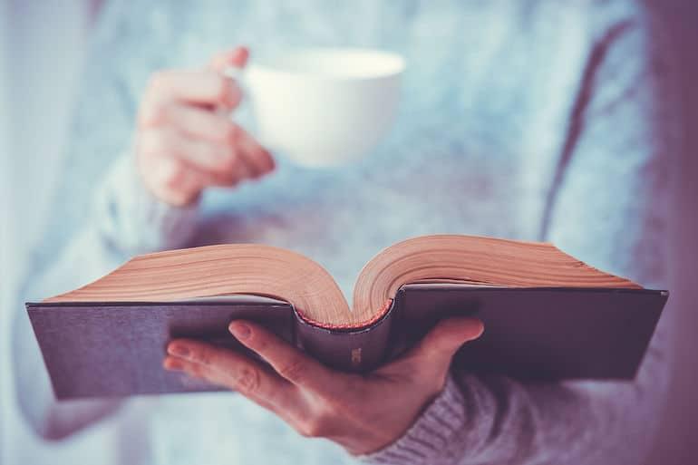 Mulher lendo livro e segurando xícara de chá.