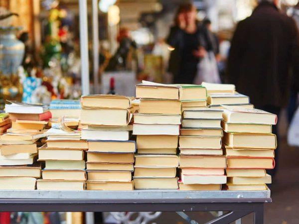 Livros empilhados sobre mesa.