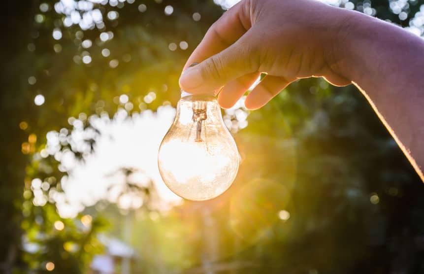 Mão segurando lâmpada com luz do sol ao fundo.