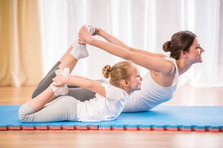 Mãe e filha praticando yoga.