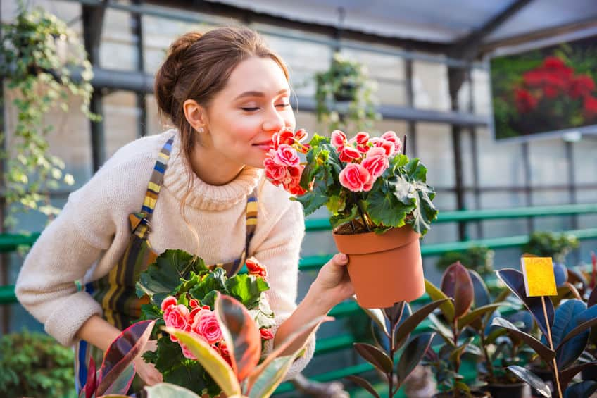 Imagem de mulher cheirando flores.