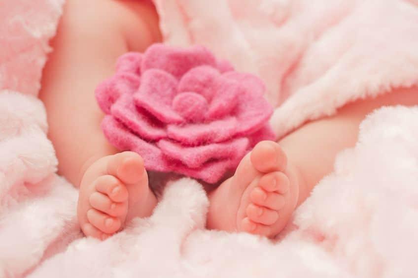 Pés de um bebê deitado numa manta com uma rosa de crochê