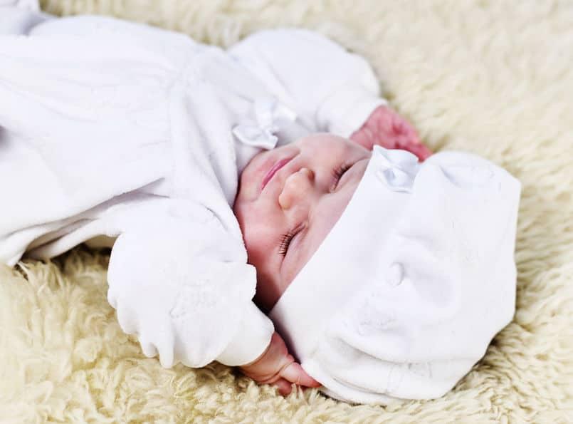 Bebê de touquinha deitado sobre uma manta